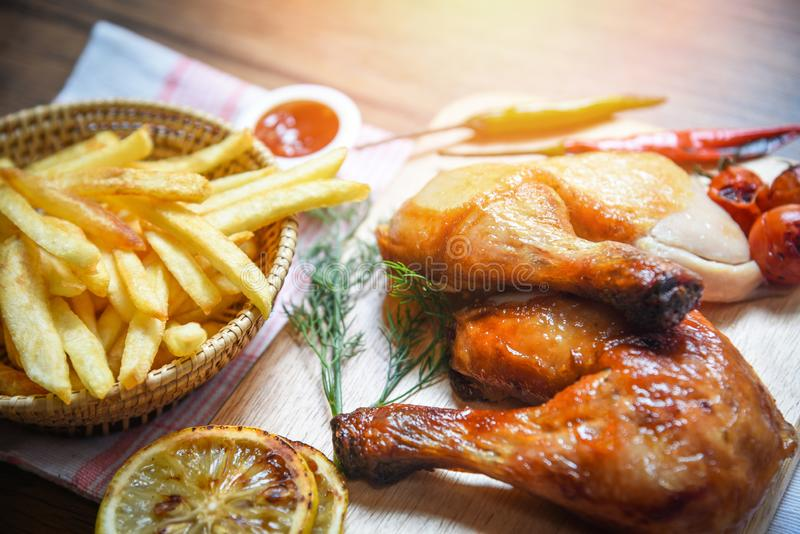 在木切板和薯条篮子的烤鸡腿用玉米柠檬辣椒辣草本香料 免版税图库摄影