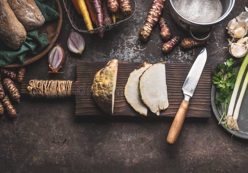在木切板的切的芹菜有在土气厨房用桌背景的刀子的与罐和其他根菜类成份 库存照片
