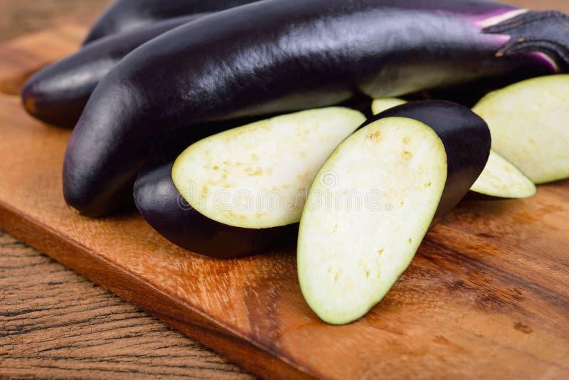 在木切板的整个和切的新鲜的长的紫色茄子 免版税库存图片