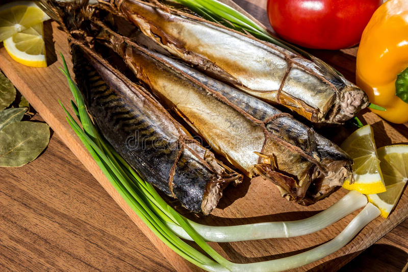 在木切板的熏制的鱼鲭鱼在菜背景以子弹密击,蕃茄,葱 免版税库存照片