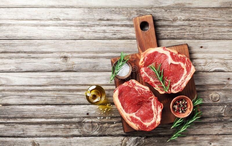 在木切板顶视图的新鲜的肉 未加工的牛排和香料烹调的 免版税库存照片