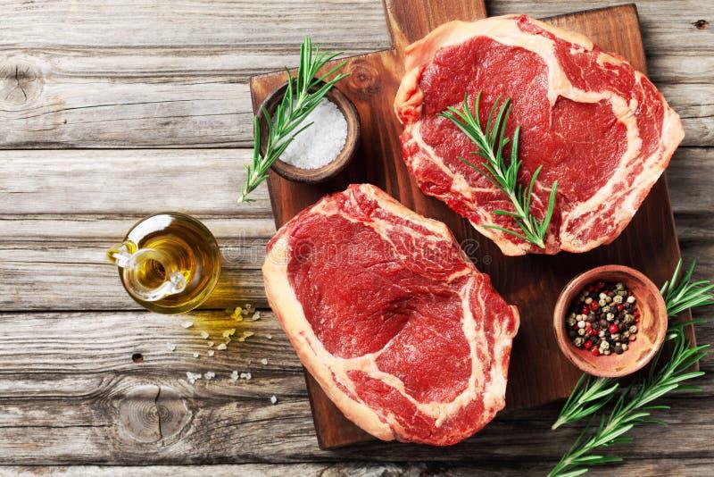 在木切板顶视图的新鲜的肉 未加工的牛排和香料烹调的 库存照片