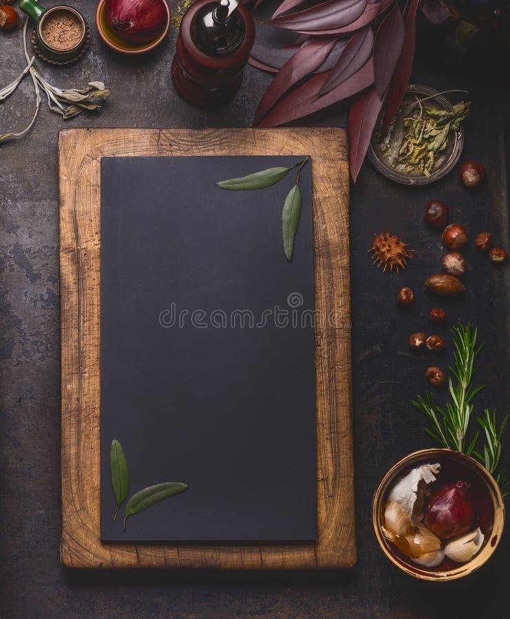 在木制框架和烹调成份的空白的黑板在黑暗的厨房用桌背景 库存照片