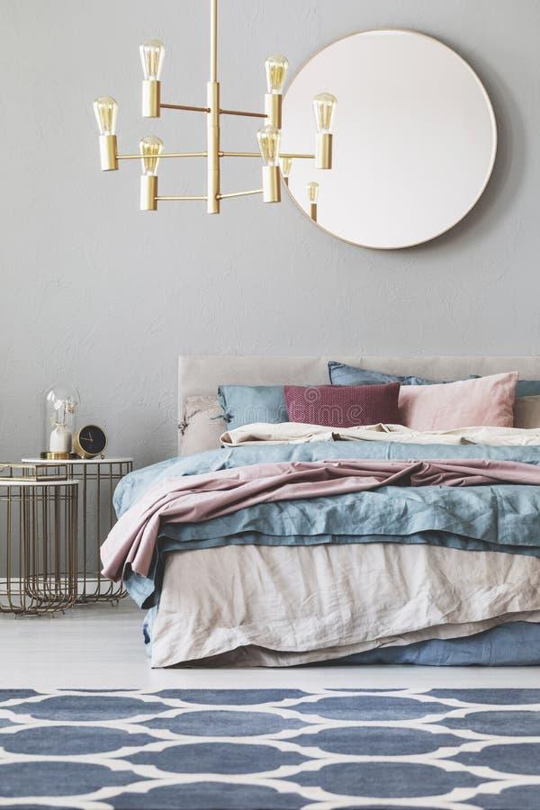 在木制框架的圆的镜子在与蓝色,米黄和粉红彩笔卧具的加长型的床上 库存照片