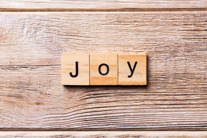 在木刻写的喜悦词 在木桌您desing的,概念上的喜悦文本 库存图片