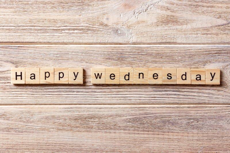 在木刻写的愉快的星期三词 在桌上的愉快的星期三文本,概念 库存图片