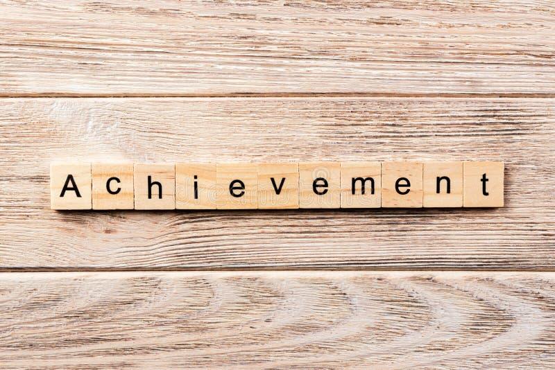在木刻写的成就词 在桌上的成就文本,概念 库存照片