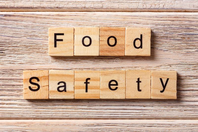 在木刻写的食品安全性词 在桌上的食品安全性文本,概念 库存照片