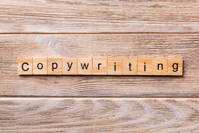 在木刻写的Copywriting词 在木桌您desing的,概念上的Copywriting文本 免版税库存照片