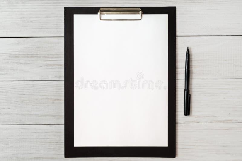 在木剪贴板的白纸有在背景的空间的 库存图片