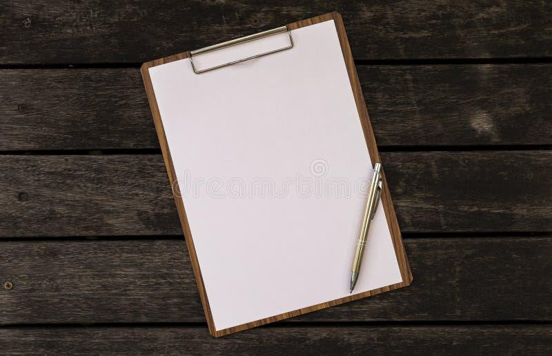 在木剪贴板的白纸在木背景 库存照片