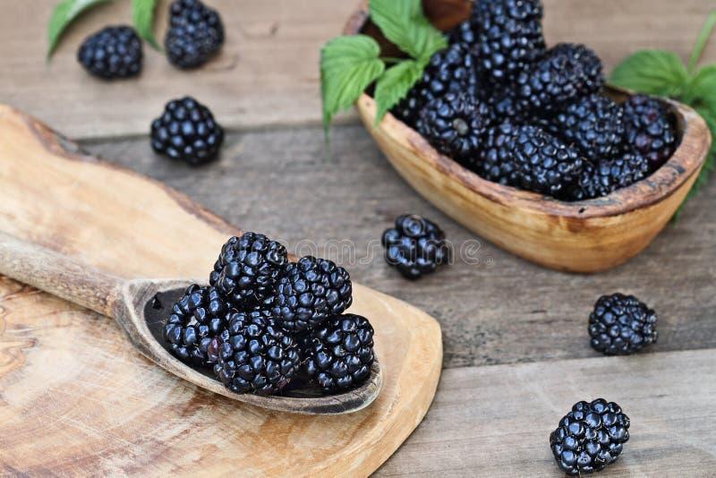 在木匙子和碗的黑莓 免版税库存照片