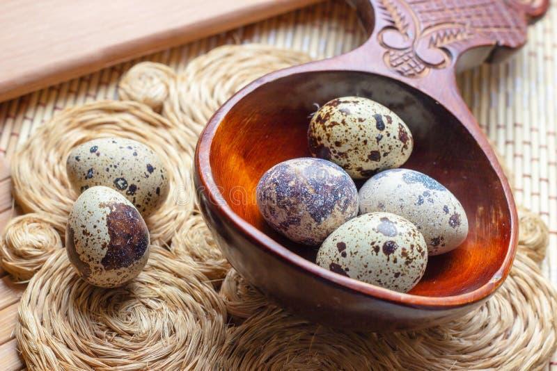 在木匙子在土气秸杆和木葡萄酒背景的新鲜的未加工的鹌鹑蛋 库存照片