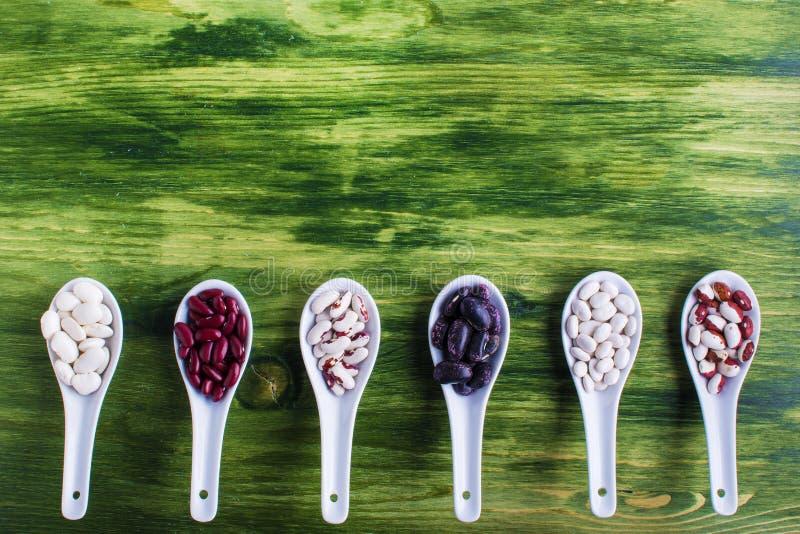 在木匙子的各种各样的干菜在绿色背景 免版税库存图片