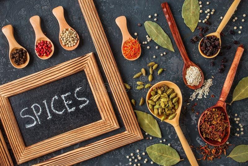 在木匙子的各种各样的香料在黑暗的石桌上 免版税库存图片
