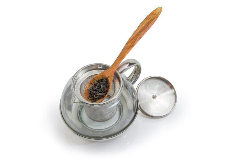 在木匙子的干茶叶在空的玻璃茶壶 免版税库存图片