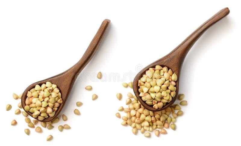 在木匙子的未煮过的荞麦,隔绝在白色背景,顶视图 免版税库存照片