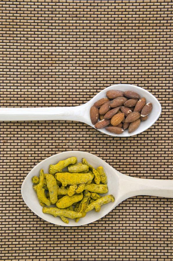 在木匙子的杏仁和姜黄(姜黄longa)干燥根 图库摄影