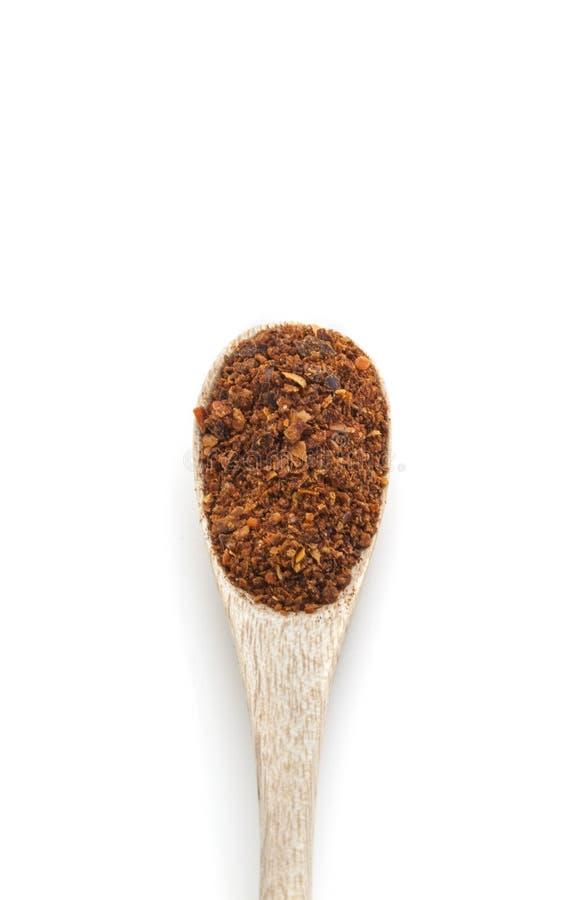 在木匙子的碎红辣椒辣椒粉香料隔绝了o 免版税库存图片