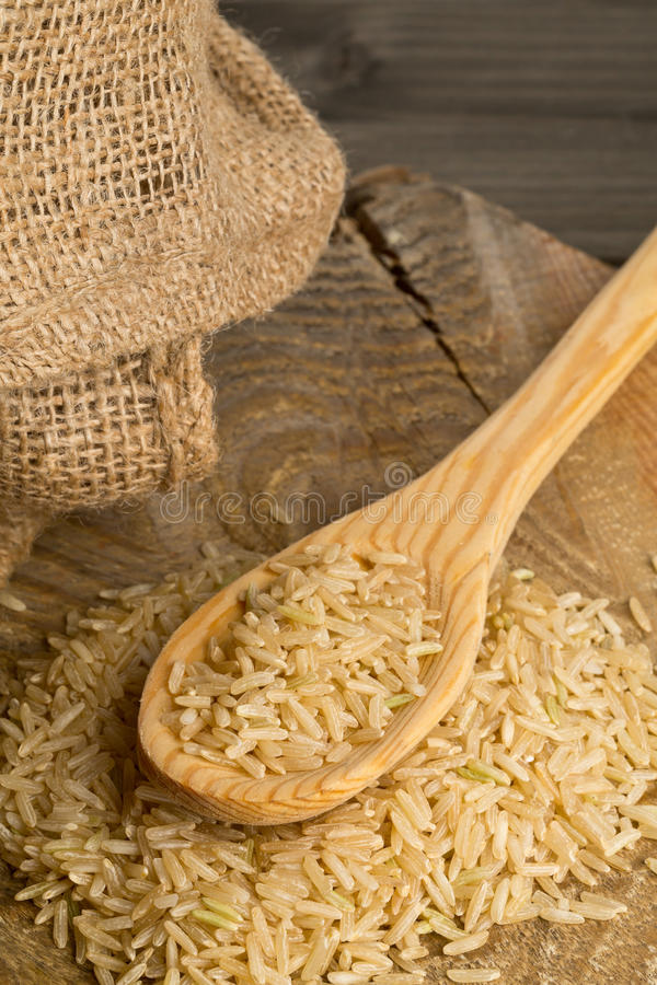 在木匙子的自然棕色未煮过的米 库存图片