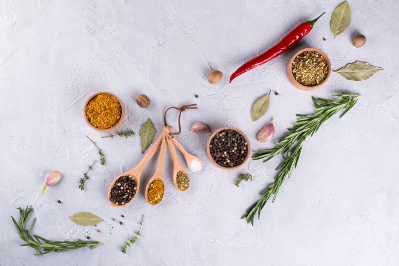 在木匙子的草本和香料选择-迷迭香,大蒜,盐,在灰色桌上的胡椒 食物舱内甲板位置 免版税库存图片