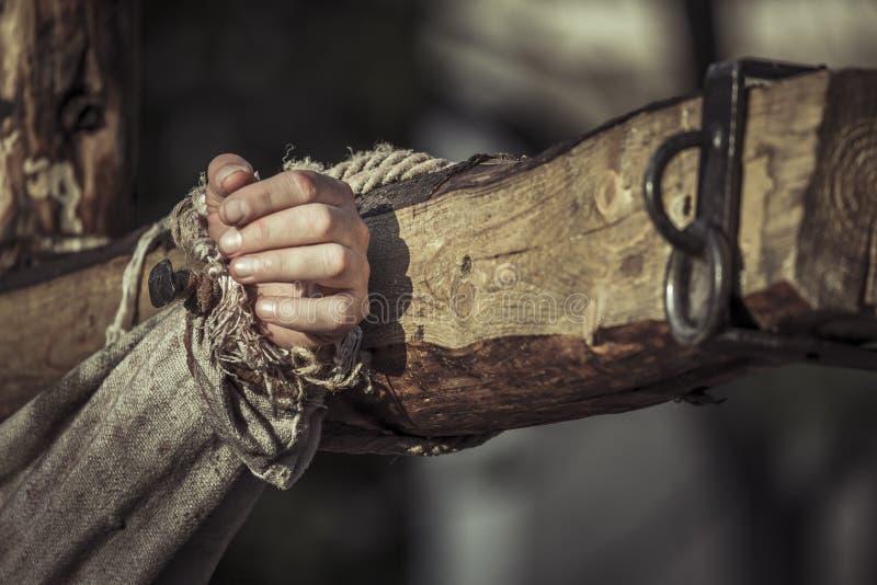 在木十字架的被钉牢的手 免版税库存照片