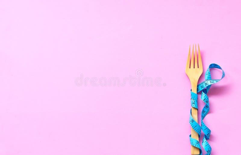 在木叉子附近被包裹的蓝色测量的磁带说谎在五颜六色的桃红色背景 库存图片