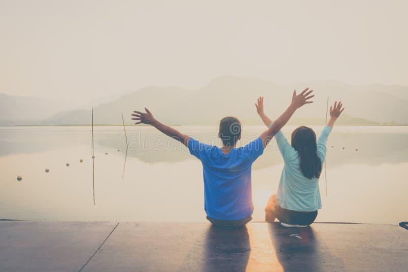 在木口岸的一对夫妇在日落的一个湖 库存照片