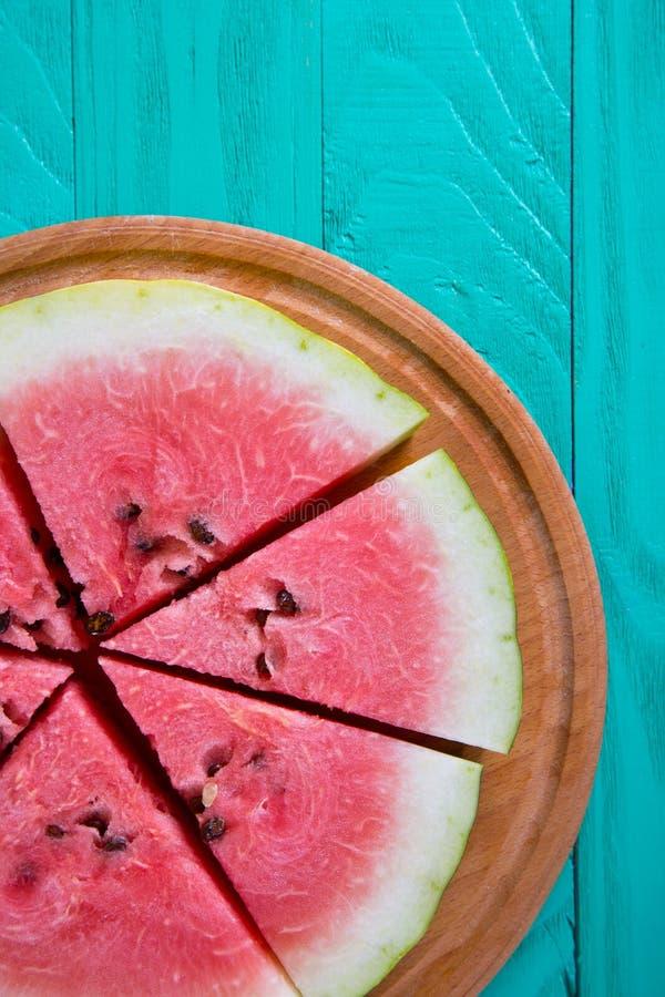 在木圆的书桌上的新鲜的切的西瓜在薄荷的绿色背景 免版税库存照片