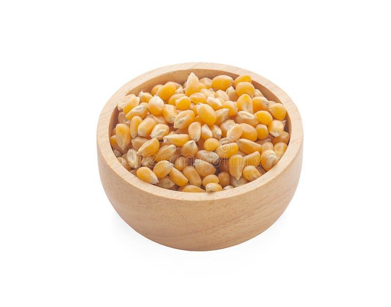 在木在白色背景玉米种子隔绝的碗和堆的玉米种子 Brot 免版税库存图片