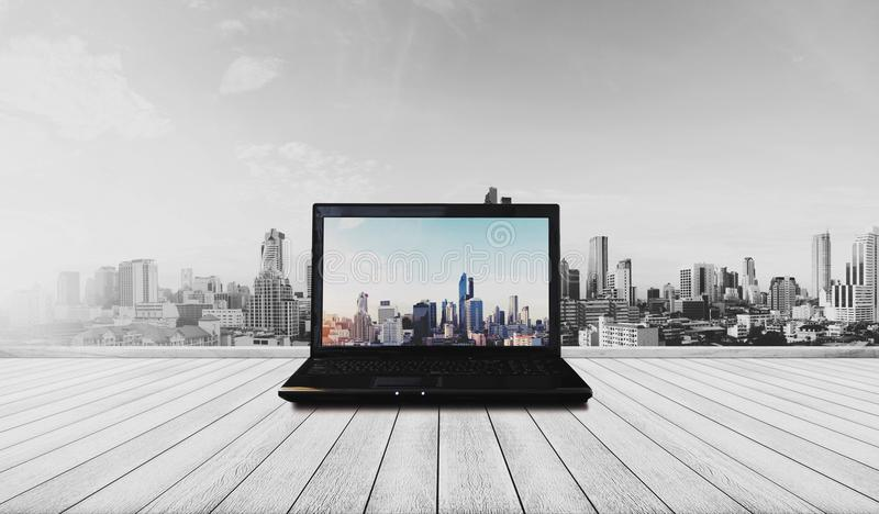 在木地板上的便携式计算机有现代城市视图 免版税库存照片
