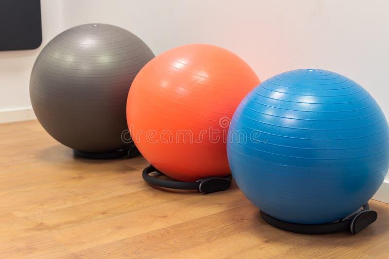 在木地板上的健身球在体育中心 与健身房球的锻炼 健身锻炼的健身房 五颜六色的健身设备 免版税库存图片