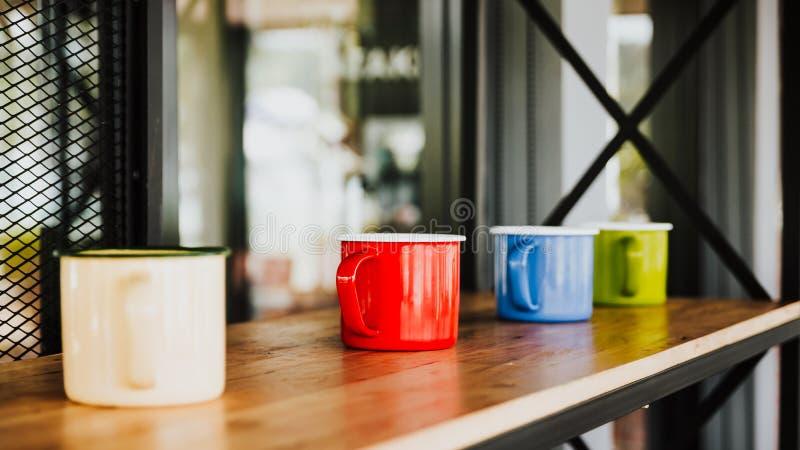 在木地板上的四个五颜六色的咖啡杯在豪华咖啡店 库存图片