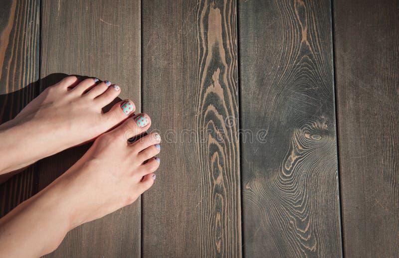 在木地板上的妇女脚 免版税库存照片