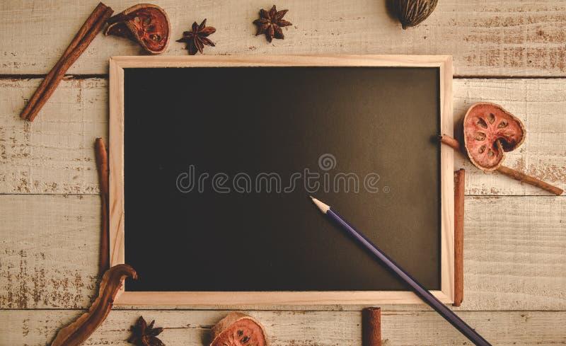 在木地板上的学校空的木黑板与铅笔和干燥叶子 教育和自然概念 回到学校题材 ?? 免版税库存图片