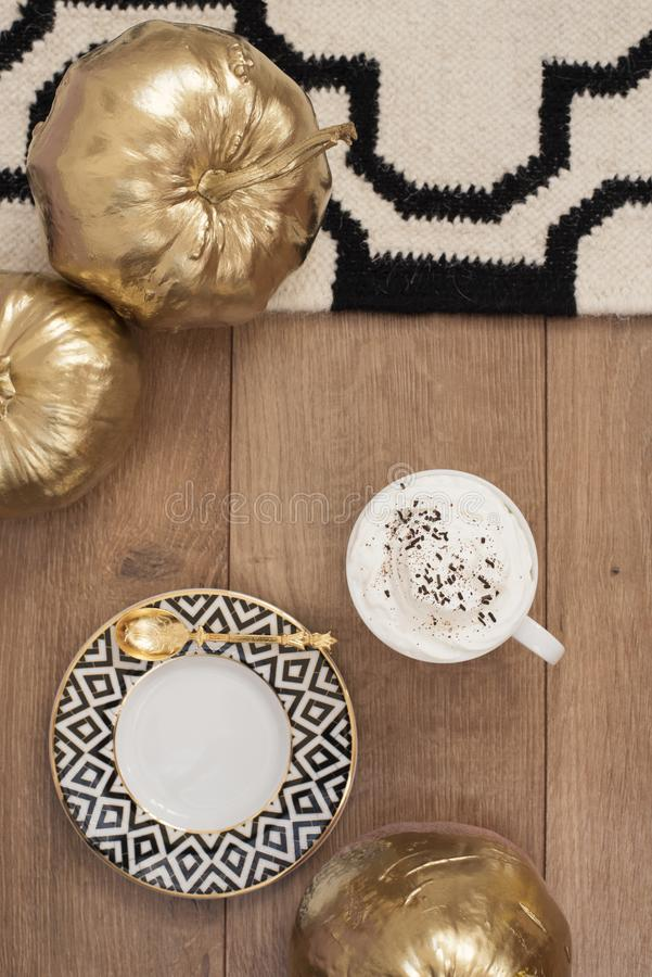 在木地板上的热奶咖啡和金南瓜 条纹设计 库存照片