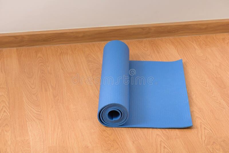 在木地板上的瑜伽席子 免版税库存照片