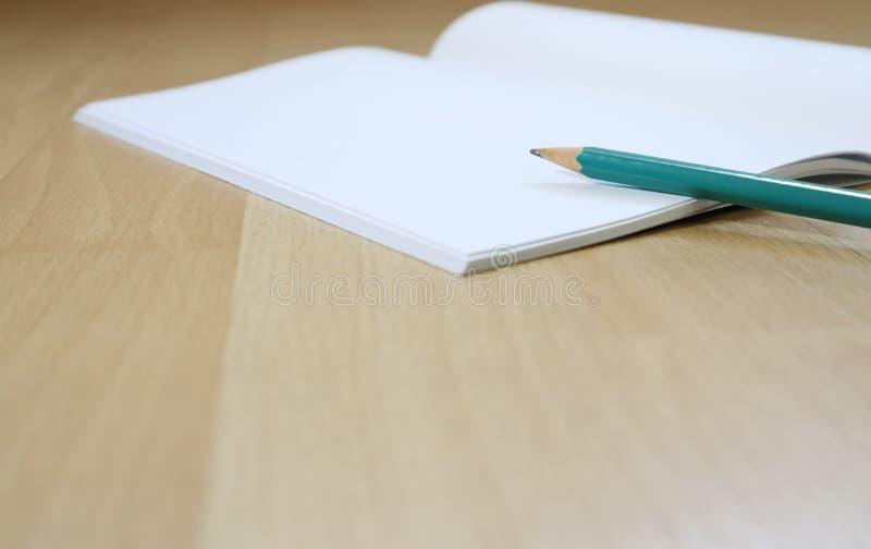 在木地板上的笔记本和笔cil 库存照片
