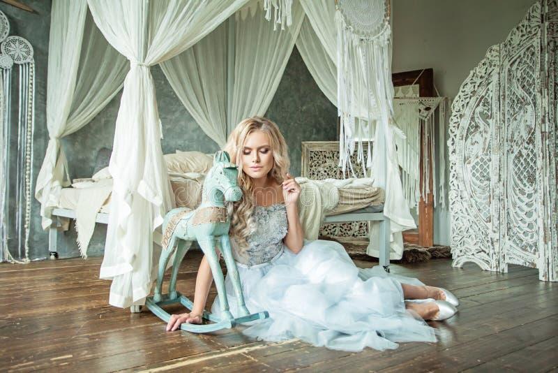 在木地板上的肉欲的Blondie妇女时装模特儿 免版税库存照片