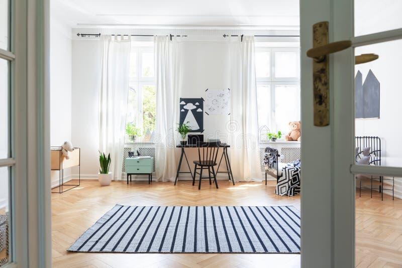 在木地板上的镶边地毯在与椅子的宽敞孩子` s室内部在书桌和海报 图库摄影