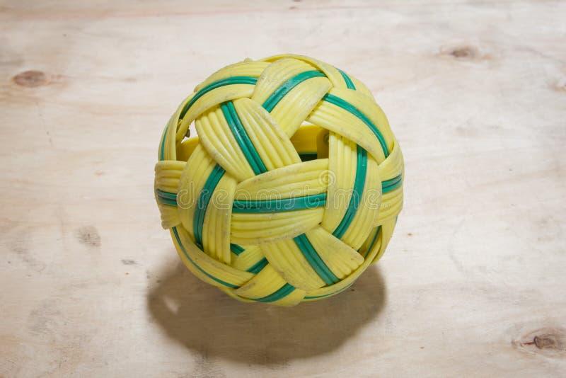 在木地板上的绿色和黄色藤条球 库存照片