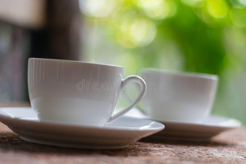 在木地板安置的2个咖啡杯在绿色自然后 免版税库存照片