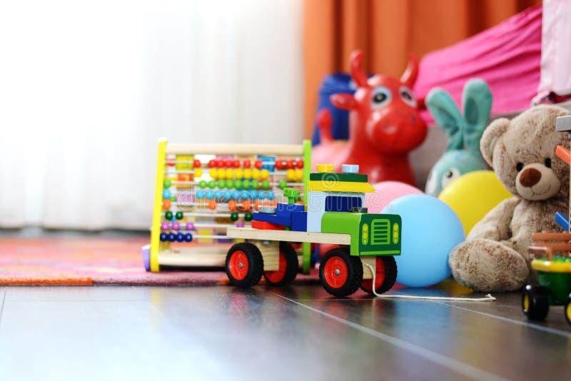 在木地板或地毯上的Children's多彩多姿的玩具在孩子室 库存照片