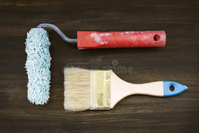 在木地板,漆滚筒,刷子,顶视图上的绘画工具 库存图片