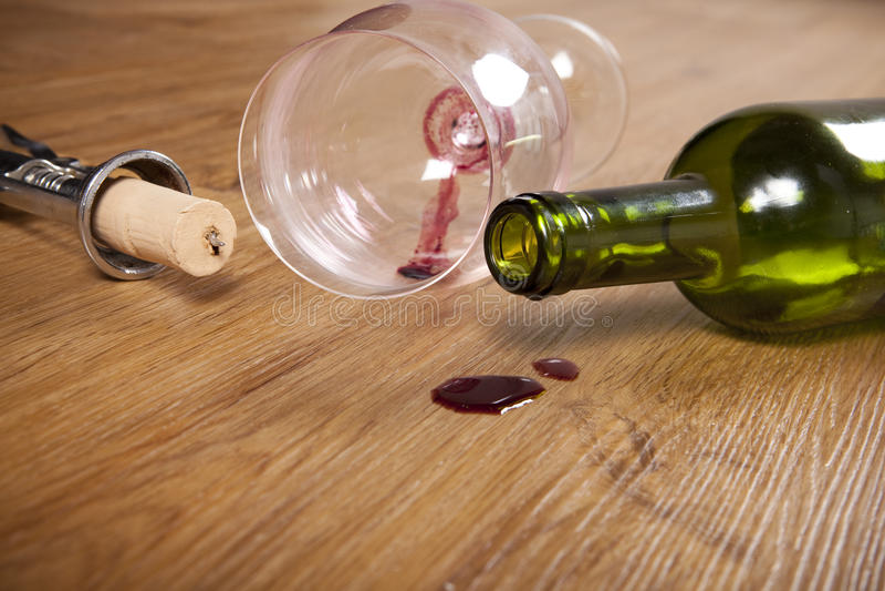 在木地板,肮脏的酒杯,拔塞螺旋,空的酒瓶的红葡萄酒污点 库存照片