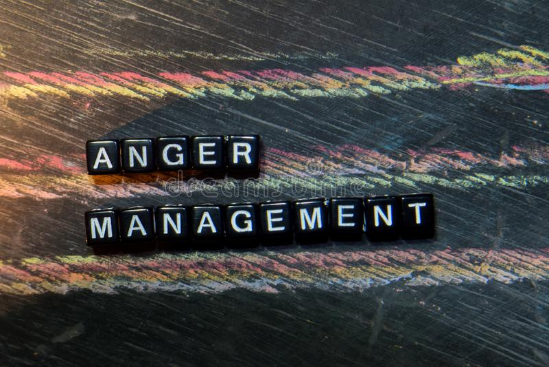 在木块的愤怒管理 发怒被处理的图象有黑板背景 免版税库存图片