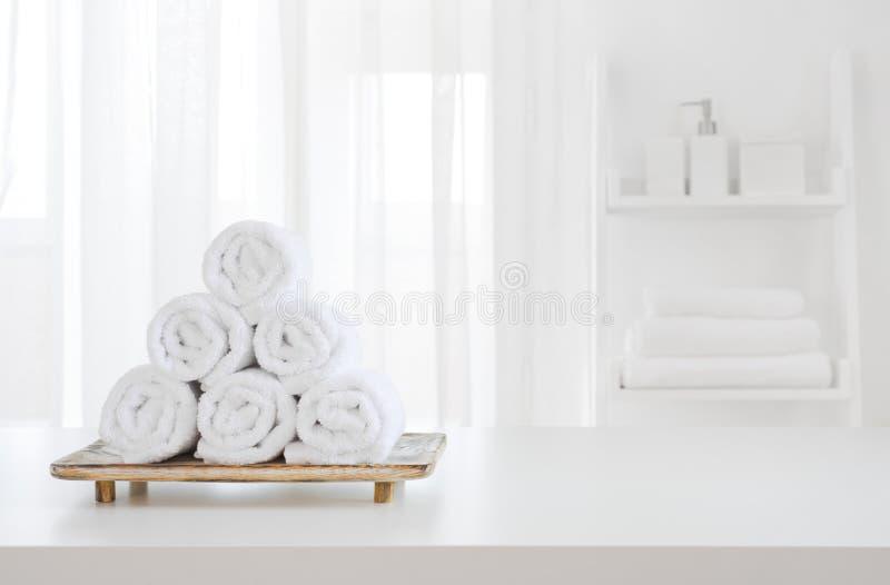 在木垫座的白色毛巾在被弄脏的温泉室背景 库存照片