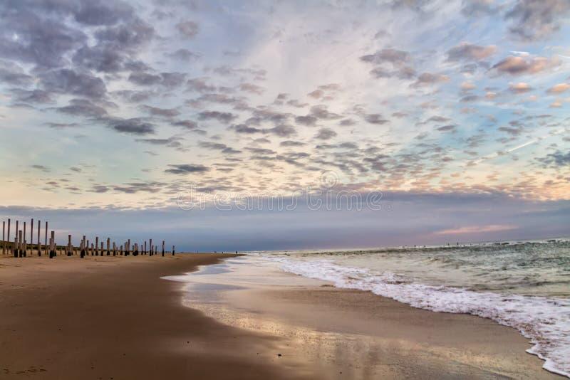 在木堆的美丽的剧烈的多云天空从海滩 免版税库存照片