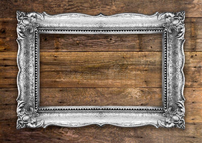 在木墙壁上的减速火箭的银色画框 免版税库存图片