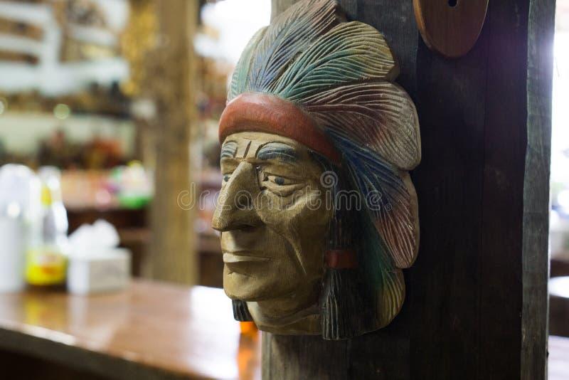 在木墙壁上的印地安木面孔 免版税库存照片
